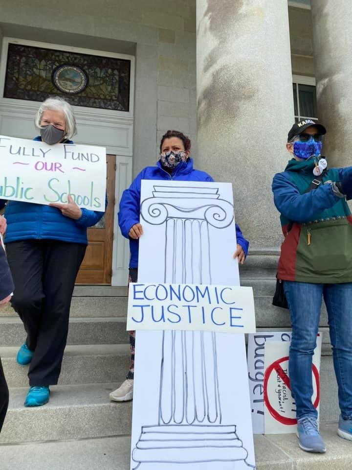 State Rep. Maria Perez holds Economic Justice Pillar sign